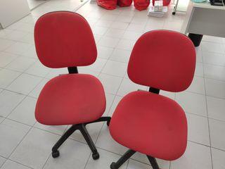 Dos sillas de oficina rojas con ruedas.