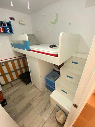 Cama alta, con armarios y estantería.