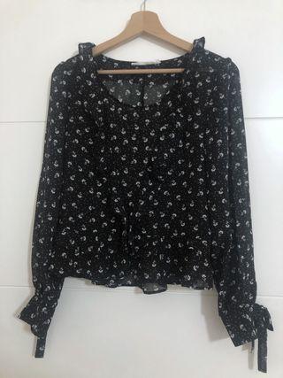 Blusa negra con detalles florales blanco de Sfera