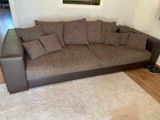 Sofá marrón con 11 almohadas