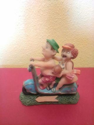 Figura decorativa de una pareja con niño en moto