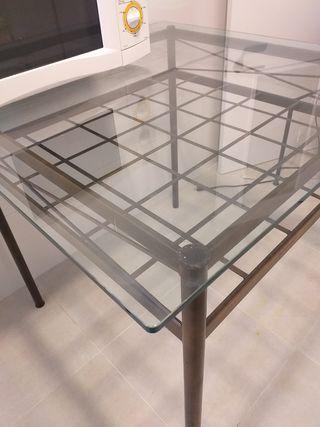 Mesa de hierro con cubierta de cristal.