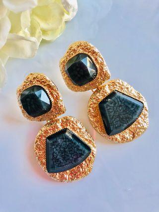 Pendientes dorados con piedras negras.