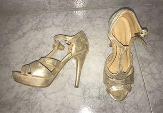 Zapatos tacón alto dorados.