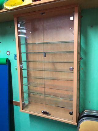 Vitrina expositora de madera y puerta de cristal.