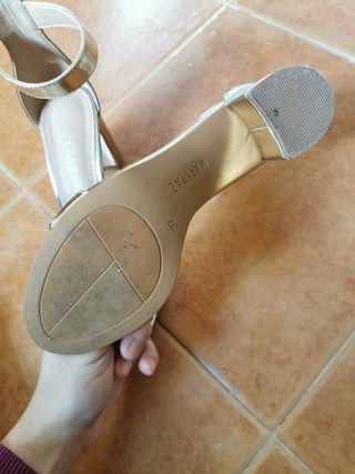 Zapato de tacón dorado.