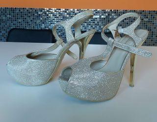 Zapatos sandalia dorados de tacón alto y fino.