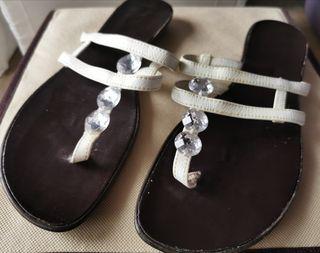 Sandalias planas de piel blanca y brillantes