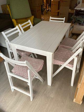 Mesa de madera natural con sillas y cojines