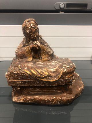 Escultura de señora apoyada en una piedra