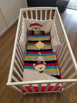 cuna de bebe con juego de sábanas y chichonera.