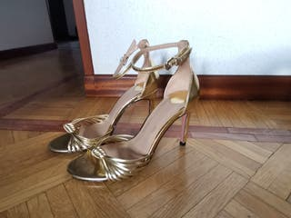 sandalias doradas de tacón.