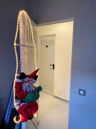Papá Noel con escalera y luces exterior