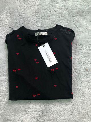 Camiseta transparente con corazones rojos