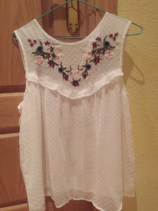 Blusa plumeti blanca con flores bordadas.