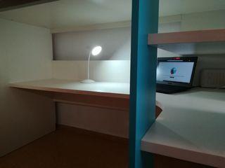 Dormitorio juvenil azul con cama sobre escritorio