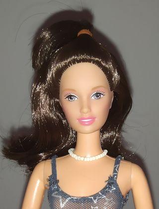 Muñeca Barbie castaña con brazos articulados.