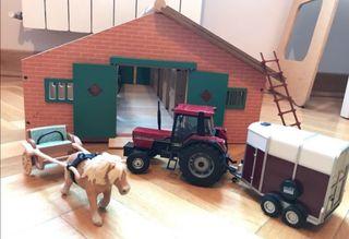 Cuadra de madera con tractor, carreta y caballo.