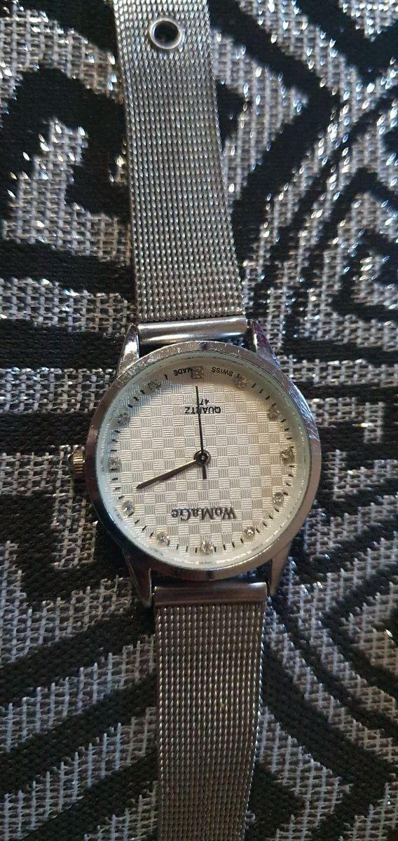 Reloj plateado y colgante piedra
