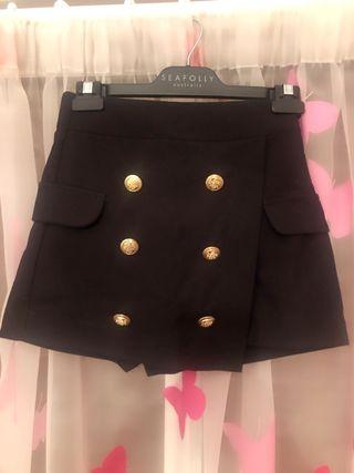 Bermuda tipo falda con botones dorados