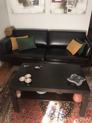 Sofá cama de piel marrón oscuro y mesa