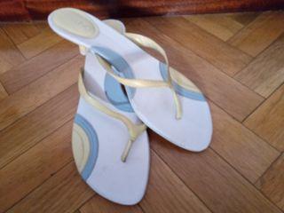 Sandalias amarillas de dedo con tacón pequeño.