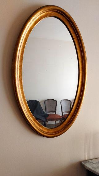 Espejo ovalado con marco dorado acabado en madera.